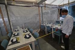 Un ristoratore verifica il distanziamento dei tavoli